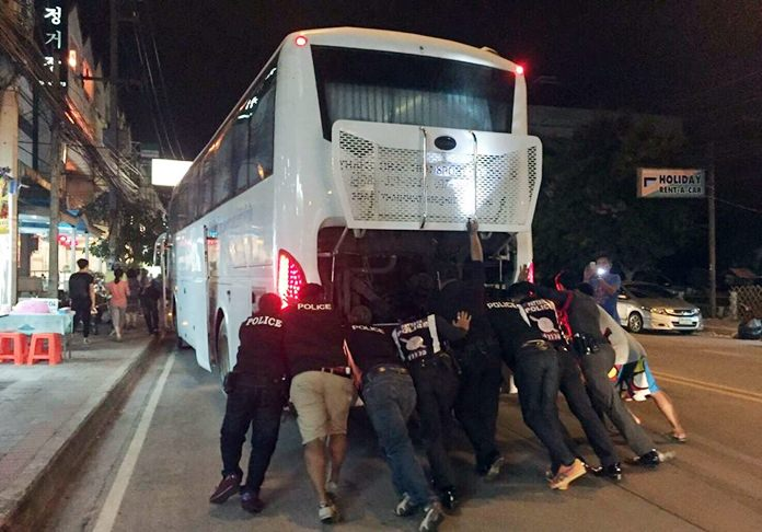 Pattaya police officers put their backs into their work when a tour bus broke down on Third Road, pushing the idled coach out of traffic.