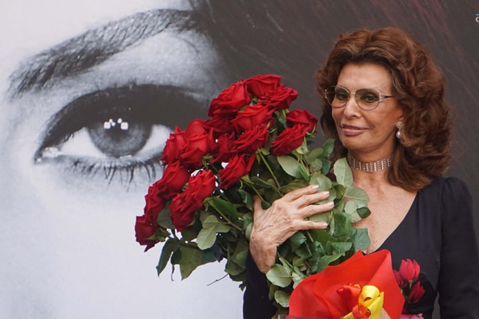 Sophia Loren holds a bunch of red roses as she stands in front a giant portrait of herself after being awarded with the honorary citizenship of Naples, Italy, Saturday, July 9. (Cesare Abbate/ANSA Via AP)