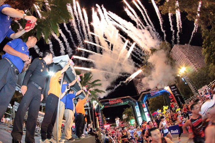 Fireworks explode across the sky as a multitude of runners, joggers and walkers cross the start line on Beach Road during the 2016 edition of the annual Pattaya City Marathon held in the early hours of Sunday morning, July 17.