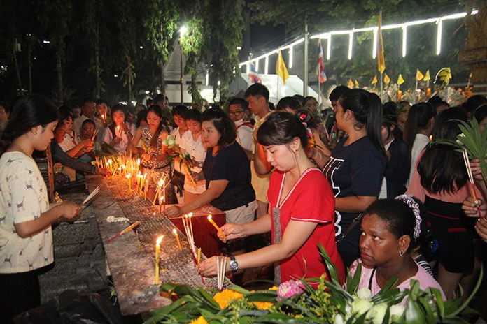 Buddhists light candles and incense to make merit at Wat Chaimongkol in South Pattaya.