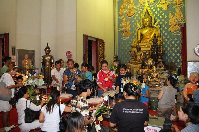 Buddhists make merit inside Wat Chaimongkol in South Pattaya.