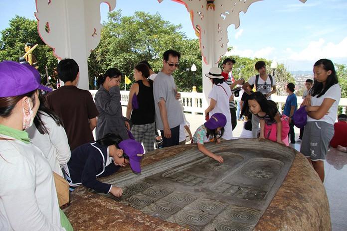 Families study Buddha's footprint at the top of Big Buddha Hill in South Pattaya.