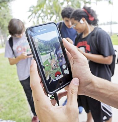 """In this Tuesday, July 12, 2016, file photo, Pinsir, a Pokemon, is found by a group of Pokemon Go players at Bayfront Park in downtown Miami. The """"Pokemon Go"""" craze has sent legions of players hiking around cities and battling with """"pocket monsters"""" on their smartphones. (AP Photo/Alan Diaz, File)"""