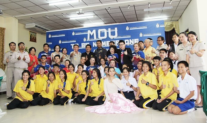 Students from Pattaya School 11 pose for a group photo with members of the World Vison Foundation and local police and communities after signing an agreement to help battle drug use.