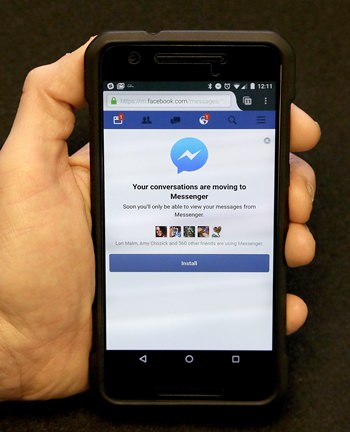 An Associated Press reporter holds a mobile phone showing the Facebook Messenger app installation page in San Francisco, Wednesday, July 27, 2016. Facebook is pushing more people to install its Messenger application, now by blocking people who want to send and receive messages via its mobile website instead of the app. (AP Photo/Jeff Chiu)