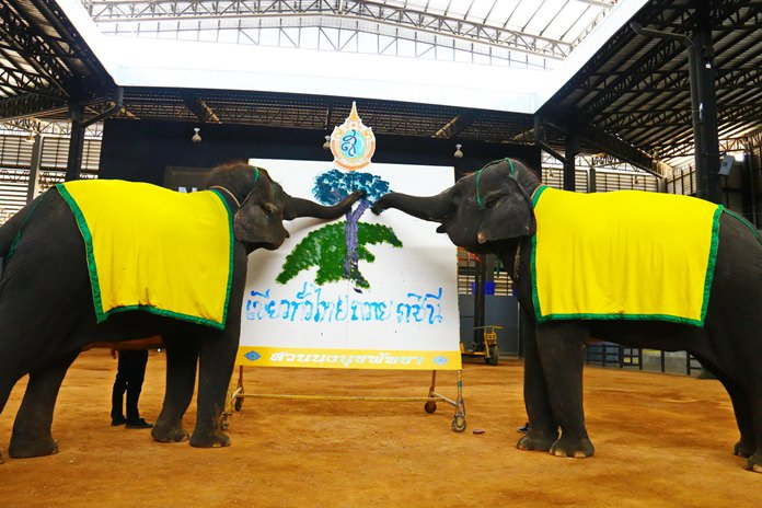 "Two elephants write ""green across Thailand to dedicate to HM the Queen"" with their trunks."
