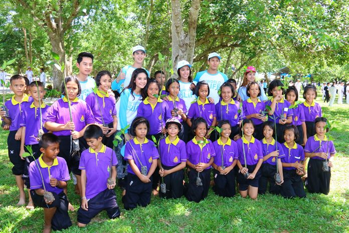 Celebrities pose with school children before the latter rolled up their pant legs and planted mangroves in the mud.