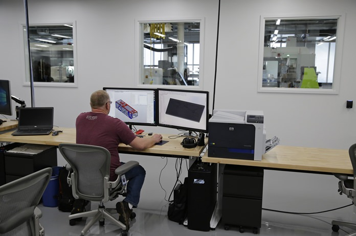 In this photo taken Tuesday, Aug. 2, 2016, a Facebook book employee works inside Area 404, the hardware R&D lab, at their headquarters in Menlo Park, Calif. (AP Photo/Eric Risberg)