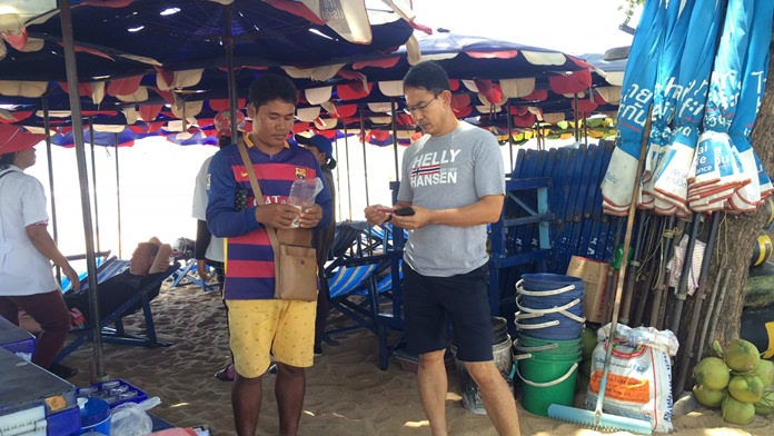 Cambodian vendor Sonauean Aoen (left) has been reprimanded for chasing away tourists who opted to bring their own towel and not rent a beach chair from him.