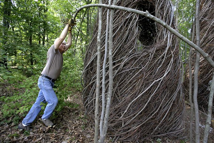"""Sculptor Patrick Dougherty bends a sapling while constructing a sculptural installation """"The Wild Rumpus,"""" from branches and sticks on the grounds of the Tower Hill Botanic Garden, in Boylston, Mass. (AP Photo/Steven Senne)"""