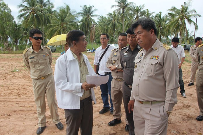 Former chairman of the Pattaya City Council Tavich Chaiswangwong (left, wearing white jacket) explains the history behind the barrels disposed on his land.