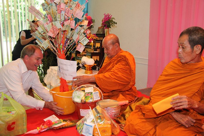 Robert Rijnders (left) lead the Amari staff in presenting alms to revered monks invited for the ceremony.