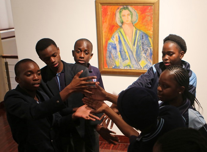 Students from the New Model School pose for a photo in front of a work by artist Henri Matisse in Johannesburg, South Africa. (AP Photo/Denis Farrell)