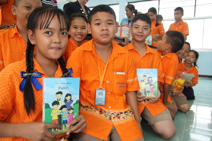 Students ham it up for the camera to show how happy they are to receive these new books.