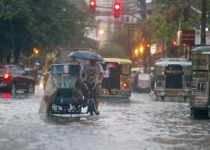 In this Aug. 26, 2016 file photo, commuters and motorists go on their way as heavy monsoon rains inundate low-lying areas in Manila, Philippines. Typhoons that slam into land in the northwestern Pacific - especially the biggest tropical cyclones of the bunch - have gotten considerably stronger since the 1970s, a new study concludes. (AP Photo/Bullit Marquez, File)