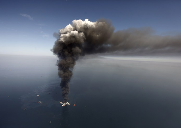 This April 21, 2010, file photo shows a large plume of smoke rising from BP's Deepwater Horizon offshore oil rig in the Gulf of Mexico. (AP Photo/Gerald Herbert)