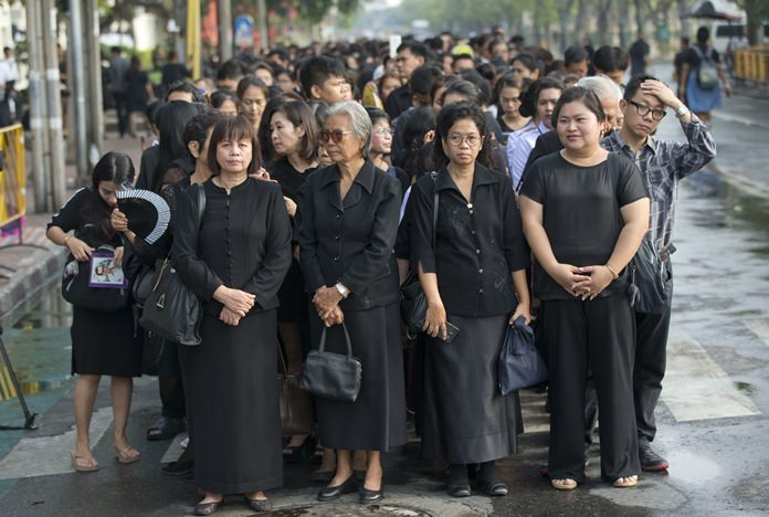 Thai people stand in lines to offer condolences for HM King Bhumibol Adulyadej at Grand Palace in Bangkok, Friday, Oct. 14. Grieving Thais went to work dressed mostly in black Friday morning, just hours after the palace announced the death of their beloved King, the the world's longest-reigning monarch. (AP Photo/ Gemunu Amarasinghe)