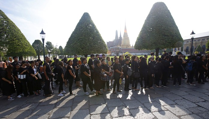 People dressed mostly in black line up to offer condolences for HM King Bhumibol Adulyadej at Grand Palace in Bangkok, Thailand, Friday, Oct. 14, 2016. (AP Photo/Sakchai Lalit)