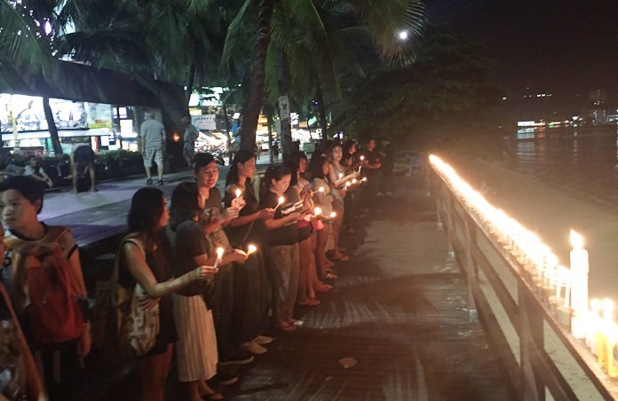 Residents join to light candles to guide HM the King to heaven at the Sailboat Monument.