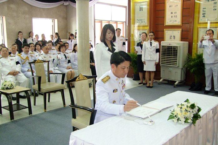 Chonburi Gov. Pakarathorn Thienchai signs a book of condolences at the provincial hall.