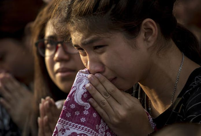 A Thai woman cries as she clasps hands with others to pay her last respects to a van carrying the body of the late King Bhumibol Adulyadej driving past outside Grand Palace in Bangkok. (AP Photo/Wason Wanichakorn)