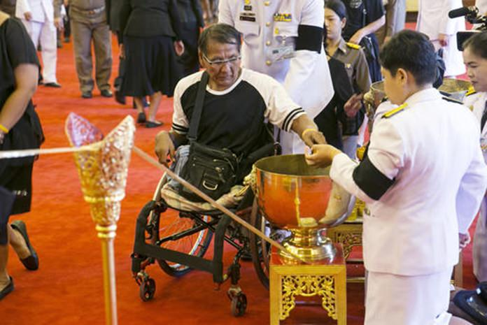 A mourner, center, pours holy water into a bowl as part of a bathing ceremony for Thai King Bhumibol Adulyadej at the Grand Palace in Bangkok. (AP Photo/Wason Wanichakorn)