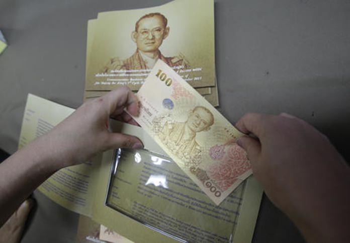 A mourner inserts a commemorative banknote of Thai King Bhumibol Adulyadej in Bangkok.(AP Photo/Sakchai Lalit)
