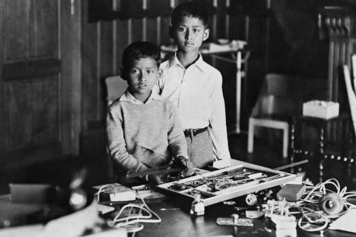 In this Sept. 22, 1935, file photo, ten-year-old King Ananda Mahidol of Siam, now known as Thailand, right, stands with his brother Prince Bhumibol, while playing with presents including a science kit he received on his tenth birthday, in Lausanne, Switzerland. (AP Photo, File)