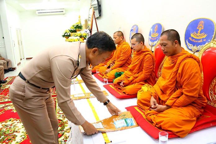 Rear Adm. Yuth Pichitchumpol presents robes to monks at the 1st Naval Area Command in Bang Saray.