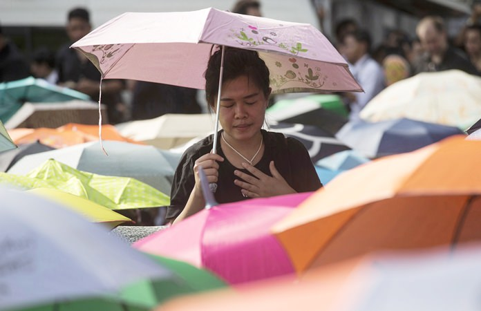 A Thai woman holds an umbrella as she waits to pay last respects to the late HM King Bhumibol Adulyadej outside the Grand Palace. The United Nations paid tribute to the late HM King Bhumibol Adulyadej on Friday, Oct. 28, with a moment of silence and speeches in the General Assembly Hall. (AP Photo/Wason Wanichakorn)