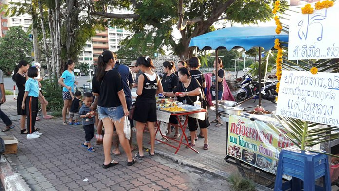 Residents of Pattaya's Keha Thepprasit Community pay tribute to HM the late King by giving away freshly cooked food for free.