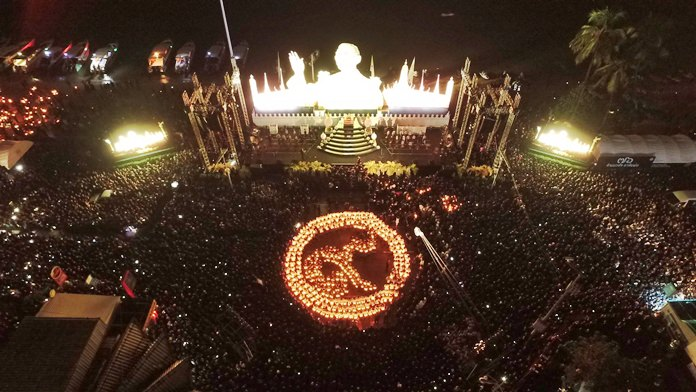 Children hold candles to form the Thai no.9 in front of a brightly lit portrait of HM the King as the whole area is kept in total darkness.