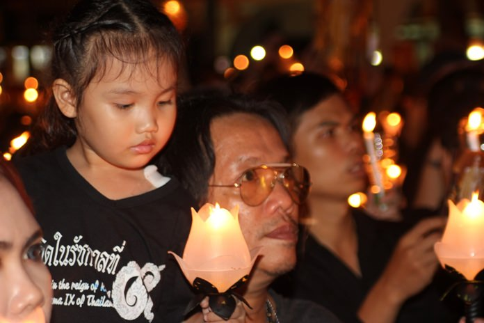 A child, who was happy to be born under the reign of King Rama IX, gets caught up in the moment.