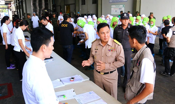 Workers line up to have their IDs checked during last week's Royal Thai Navy inspections, which led to a dozen seafood-processing factories in Samut Sakhon being shut down for labor law violations.