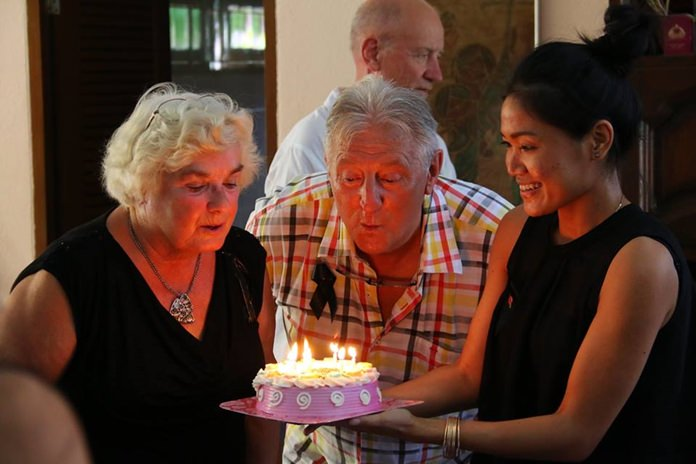 Witha Scholtes (left) and Joy Keolaphuomy help Aad Scholtes to blow out the candles on his birthday cake.