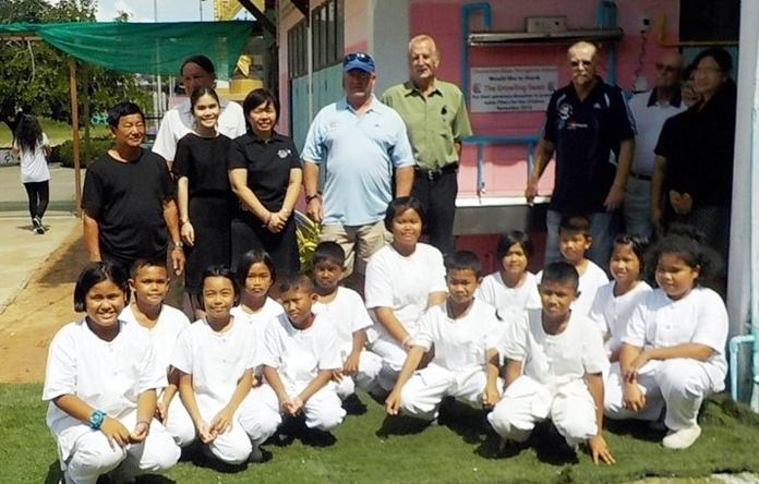 Children and teachers at Chumchon Ban Nongprue School pose for a photo with representatives from The Growling Swan golf bar.