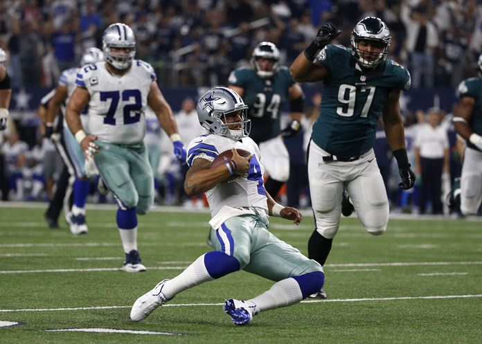 Dallas Cowboys quarterback Dak Prescott (4) slides to the ground after running the ball as Philadelphia Eagles defensive tackle Destiny Vaeao (97) gives chase in the first half of their NFL football game, Sunday, Oct. 30, in Arlington, Texas. (AP Photo/Ron Jenkins)