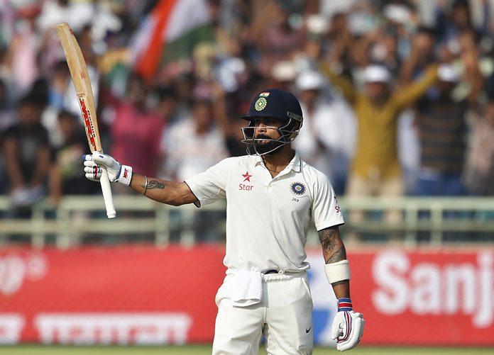 India's captain Virat Kohli raises his bat to celebrate scoring a century on the first day of the second test against England in Visakhapatnam, India, Thursday, Nov. 17. (AP Photo/Aijaz Rahi)