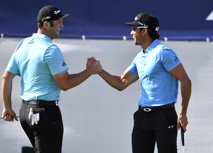 Spain's Rafa Cabrera Bello, right, is congratulated by his partner Jon Rahm after sinking a birdie putt on the 18th green during the first round of the World Cup of Golf at Kingston Heath in Melbourne, Australia, Thursday, Nov. 24. (AP Photo/Andrew Brownbill)