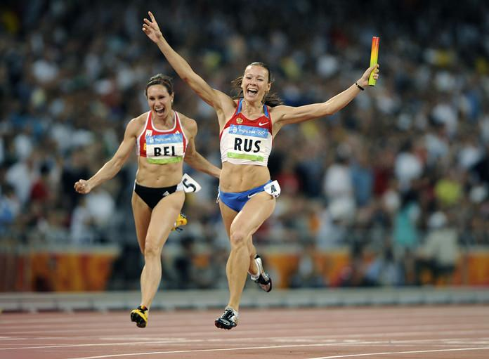 In this Aug. 22, 2008, file photo, Russia's Yulia Chermoshanskaya celebrates winning gold in the women's 4x100-meter relay final during the Beijing 2008 Olympics in China. At left is Belgium's Kim Gevaert who, along with her relay teammates from Belgium, is among the first beneficiaries of what is quickly becoming the biggest rewriting of Olympic history. (AP Photo/Mark J. Terrill)