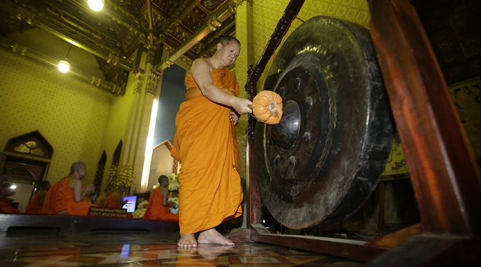 A Buddhist monk hits a gong as others pray in front of portrait HM King Maha Vajiralongkorn Bodindradebayavarangkun at the Marble temple in Bangkok, Thursday, Dec. 1, 2016. (AP Photo/Sakchai Lalit)