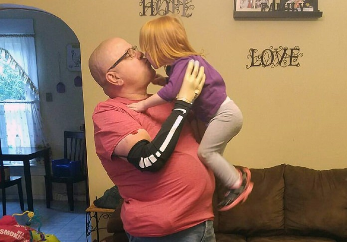 In this photo provided by James Vonderhuevel, Keith Vonderhuevel picks up 2-year-old Allison Vonderhuevel in Sidney, Ohio, using a special prosthetic hand that allowed him to feel sensation so he knew how tightly to squeeze. A next-generation artificial hand is letting amputees tell the difference between a soft or firm touch, another step toward developing prosthetics that can feel, and a natural enough sensation to hold a child without too tight a squeeze. (James Vonderhuevel via AP)