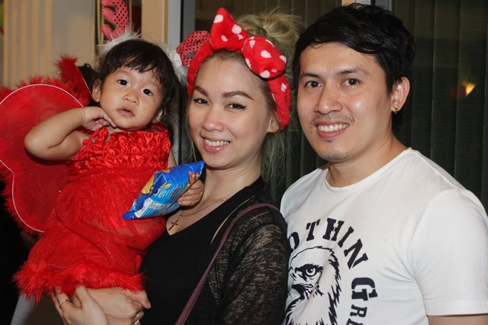 A handsome young couple and their child enjoy the Christmas spirit in church.