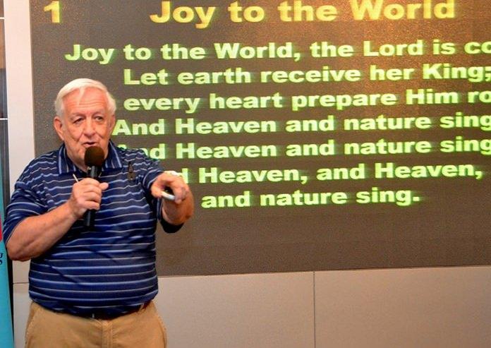 Member Roger Fox leads his fellow PCEC members and guests in singing several Christmas Carols.