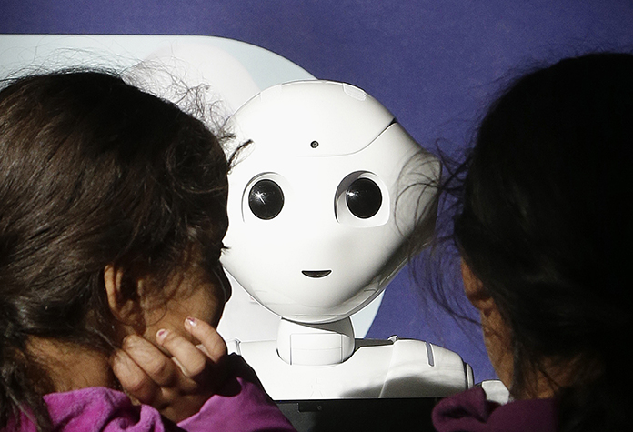 Laila, left, and her sister Nour, last names not given, play with Pepper the robot at Westfield Mall in San Francisco. (AP Photo/Jeff Chiu)