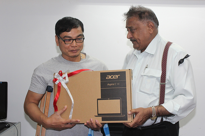 On behalf of all the employees, Peter Malhotra presents Nathakorn with a notebook computer as a parting gift.