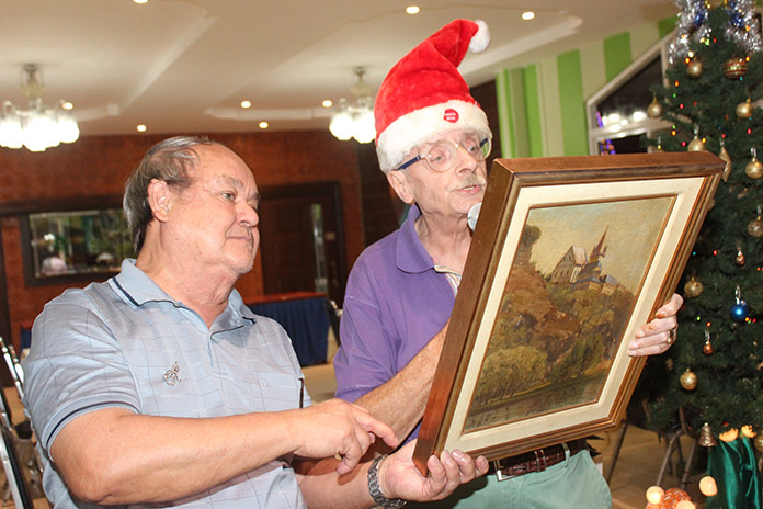 Martin Brands (right) explains details about the antique painting while Prem listens.