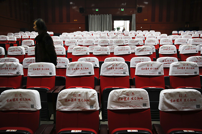 In this Dec. 12, 2016 photo, Wang Xudong, the manager of Zhuolu County Digital Cinema, checks on the main screening hall in Zhuolu county in north China's Hebei province. (AP Photo/Andy Wong)