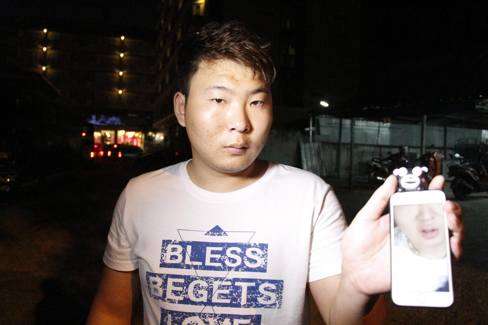 Sun Biao shows a photo of him wearing a gold chain he said was snatched by a ride by motorcycle thief.