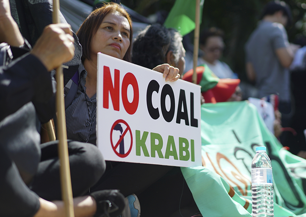 A woman holds up a sign against a proposed coal-fired plant on Thailand's coast, in Bangkok, Thailand, Feb. 17, 2017. (AP Photo/Dake Kang)
